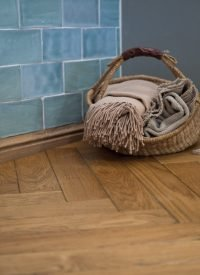 blue glazed wall tiles behind a clothes basket & timber floor